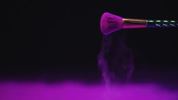 slow motion shoot of bright purple holi paint scattering from cosmetic brush