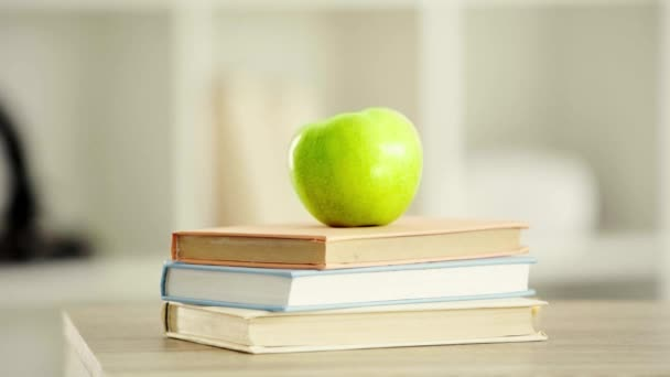 cropped view of schoolboy walking near books and taking green apple