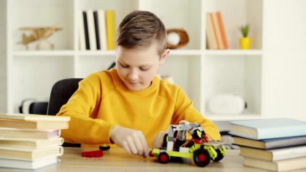 boldog gyerek játszó elektromos autó készült építőkövei könyvek közelében az asztalnál otthon