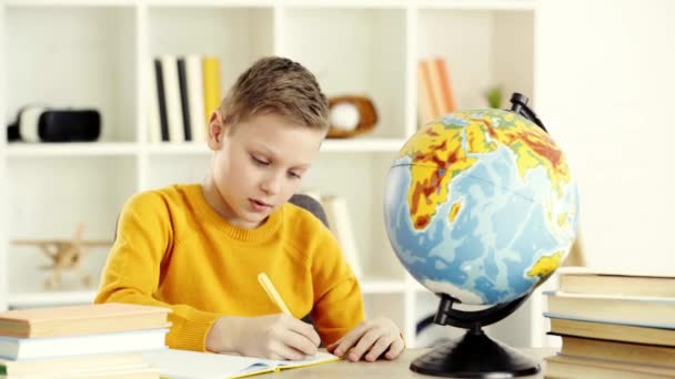 schoolboy writing in notebook and looking at globe while doing homework