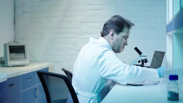 két tudós a klinikai laboratóriumban együtt mikroszkóppal kutatva