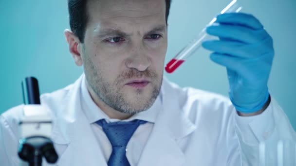 serious scientist looking at test tube with red liquid in clinical laboratory