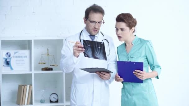 schöne Ärztin und hübsche Krankenschwester, die mit Klemmbrettern steht und spricht, während sie sich die Röntgendiagnose ansieht