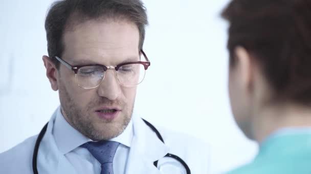 Selektiver Fokus eines gutaussehenden Arztes mit Brille im Gespräch mit Krankenschwester im Krankenhaus