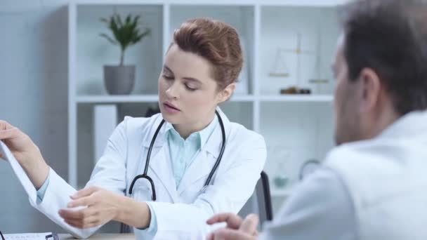 selective focus of attractive doctor holding cardiogram and talking to colleague