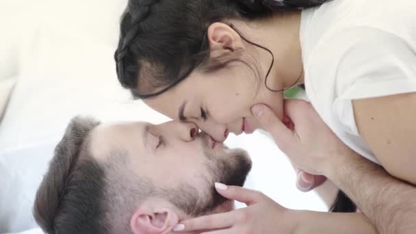 happy bearded man kissing cheeks and nose of attractive brunette girl in bedroom
