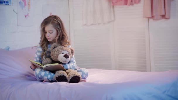 cute preteen child in pajamas sitting on bed with teddy bear and reading book
