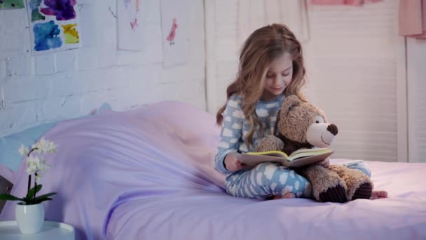 cute preteen child in pajamas sitting on bed with teddy bear, reading book, smiling and expressing amazement