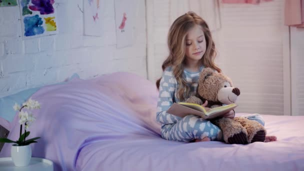 cute preteen child in pajamas sitting on bed with teddy bear, reading book, turning page and smiling in bedroom