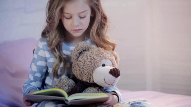 roztomilá mládež v pyžamu, která sedí na posteli s medvídkem a čte si knihu