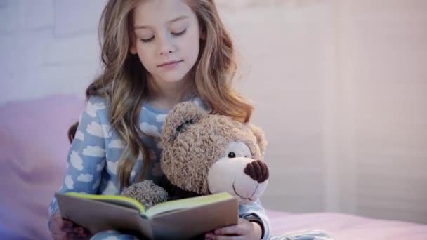 aranyos preteen gyermek pizsama ül az ágyon a mackó és nevetve olvasás közben könyv