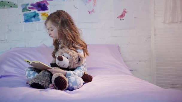 cute preteen child in pajamas sitting on bed with teddy bear, reading book and turning page