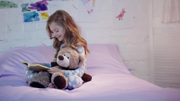 cute preteen child in pajamas sitting on bed with teddy bear and smiling while reading book