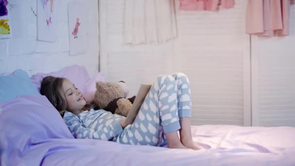 cute preteen child in pajamas lying on bed with teddy bear and smiling while reading book