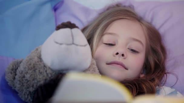 aranyos preteen gyermek pizsama feküdt az ágyon a mackó, és mosolyogva olvasás közben könyv