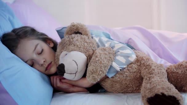 aranyos gyerek a mackó alszik az ágyban, míg a fény kikapcsolása