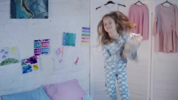 happy kid in pajamas holding teddy bear and jumping on bed in bedroom
