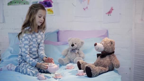 cute kid in pajamas sitting on bed and playing with toys in bedroom