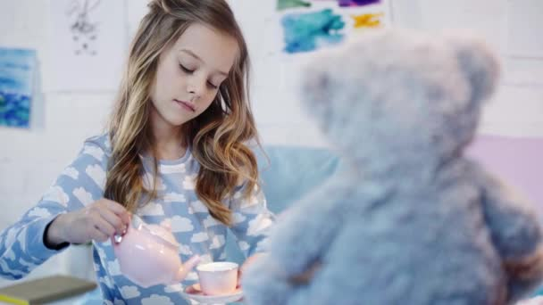 cute preteen child in pajamas sitting near teddy bear and playing with toy crockery in bedroom