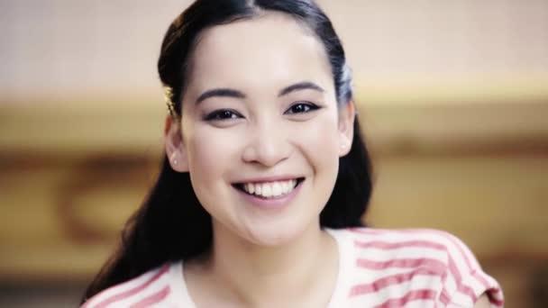 přitažlivá, brunetka, Asijská žena, která se dívá na kameru a usmívá se v kavárně