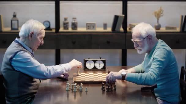 ahşap masada satranç tahtası üzerine rakamlar koyarak iki üst düzey erkek yan görünümü