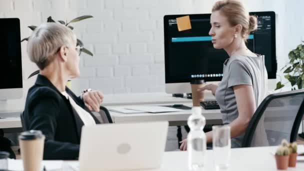 Soustřeď se na ženy, které mluví a gestikulovat, když žena v brýlích používá laptopu v kanceláři