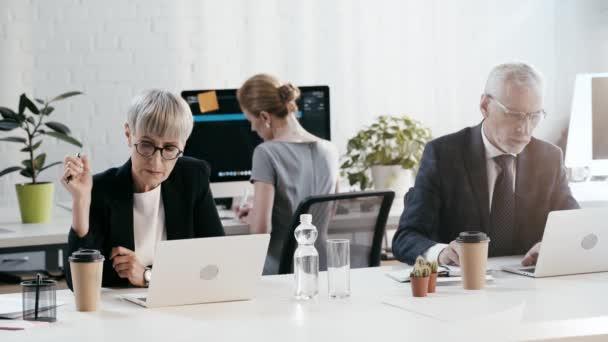 szelektív hangsúly az üzletember és üzletasszony segítségével laptopok, az ember írásban és a nők fogyasztói kávét
