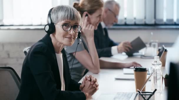 happy woman in glasses in headset with clenched hands near coworkers in office