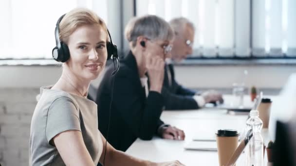 cheerful woman in headset smiling while looking at camera near coworkers in office
