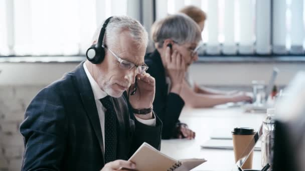 selective focus of teleworker looking at notebook while talking near coworkers, smiling and looking at camera