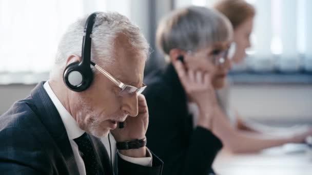 selektivní zaměření telepracovníka na brýle a náhlavní soupravu hovotující v blízkosti kolegů při konzultacích v kanceláři