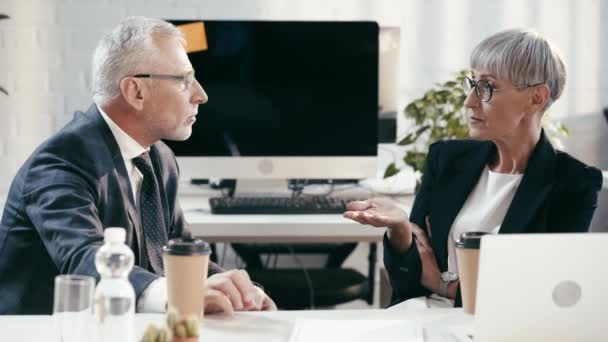 selective focus of bearded businessman gesturing while talking with attractive coworker with crossed arms