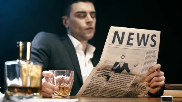 selective focus of businessman reading newspaper and drinking whiskey at table on black