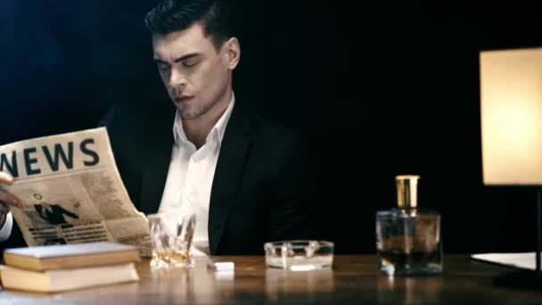 fókuszált üzletember ül asztalnál lámpával és olvasott újság fekete