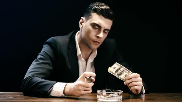 Geschäftsmann hält Feuerzeug und brennende Dollarnote über Aschenbecher an Holztisch