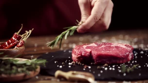 Oříznutý pohled na člověka, který mnul masový steak s rozmarí blízkými složkami