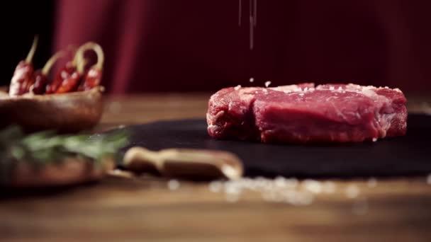 Selektive Konzentration von fallendem Salz auf rohes Fleischsteak auf dem Tisch mit Zutaten