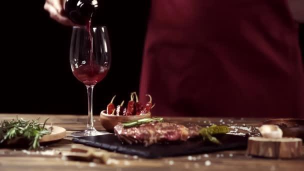 Oříznutý pohled na člověka nalévání vína ve skle blízko masových steaků a přísad na stůl izolovaný na černém