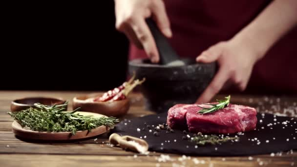 Cropped view of man grinding spices with pestle and mortar near raw meat steak and ingredients on table isolated on black