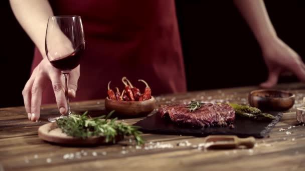 Oříznutý pohled člověka na míchání skleněného vína v blízkosti masových steaků a přísad na stůl izolovaný na černém