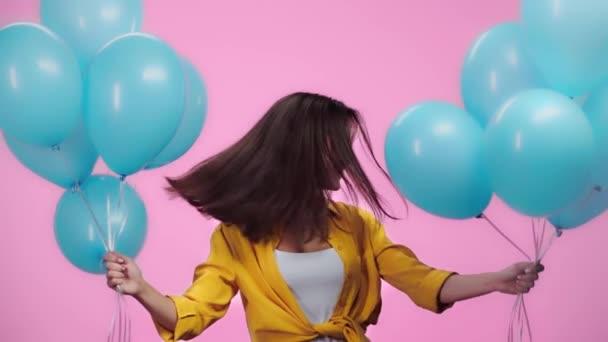 krásná dívka s balónky třesoucíma se hlavou, dívala se na kameru a usmívala se izolovaná růžová