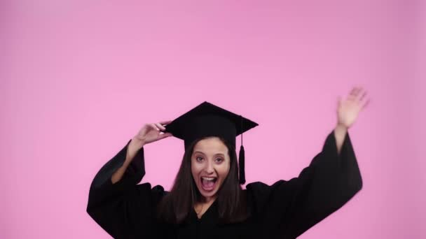 slow motion of happy student in academic gown throwing and catcing graduation cap isolated on pink