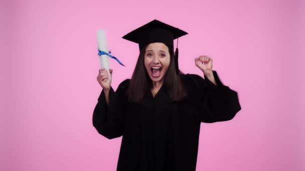 šťastný student v akademických šatech s sevřenými dlaněmi a ukazující diplom na kameru izolovaný on Pink
