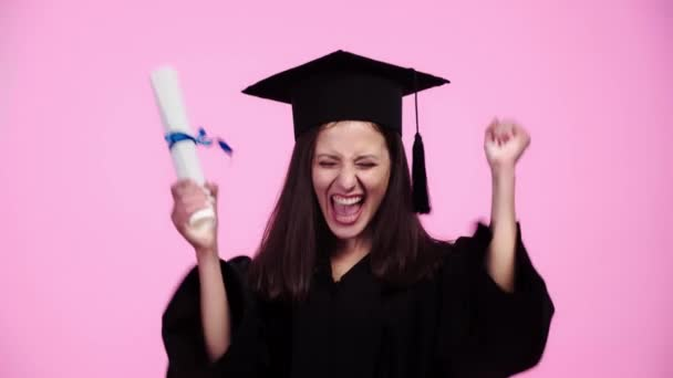 happy student in academic gown cheering with clenched hands and showing diploma at camera isolated on pink