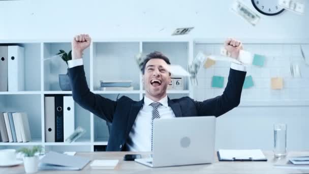 happy businessman showing winner gesture while sitting at workplace surrounded by dollar banknotes flying around