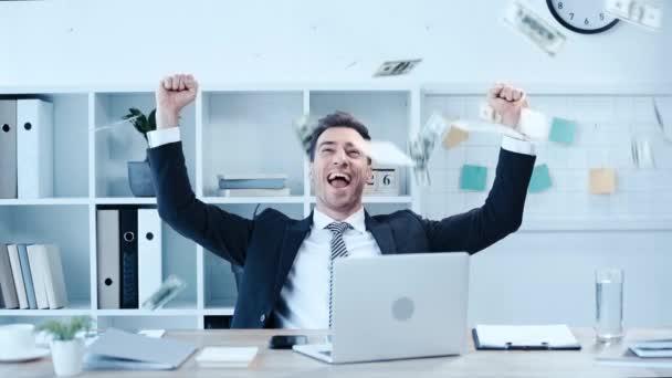 glücklicher Geschäftsmann mit Siegergeste am Arbeitsplatz, umgeben von herumfliegenden Dollarnoten