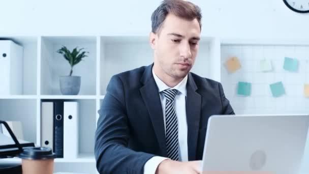 pohledný obchodník s notebookem, usměvavý a zobrazující gesto vítězů