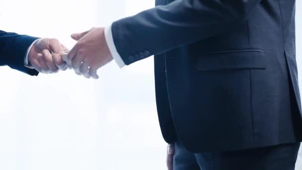 oříznutý pohled obchodníka, který dává dolarové bankovky a potřásl rukou obchodnímu partnerovi