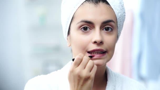 Žena v županu, aplikování rtěnky s kosmetickým kartáčkem