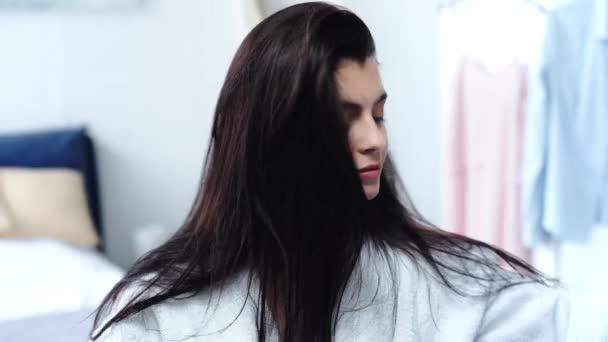 brünette Frau bürstet gesunde lange Haare mit Kamm